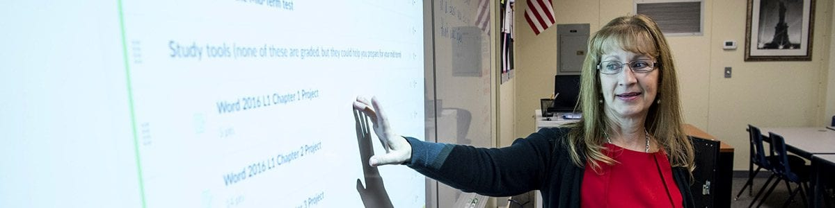 A Fresno Unified teacher going over the day's lesson using a projector