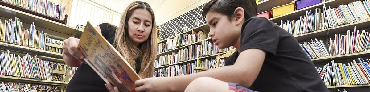 A librarian reading to a young student in the library